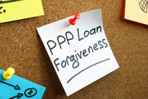 PPP loan forgiveness memo on the wooden board.